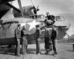 Flight crews gather around a PBY-5A Catalina patrol plane on a Marsden Mat seaplane ramp in the Aleutians, 1944-45. Note oil splatters on the hull from the notoriously leaky radial engines.