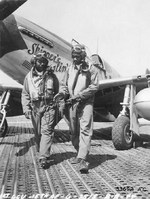"Capt Andrew D Turner, 100th Fighter Squadron CO, and Lt. Clarence P. (Lucky) Lester on the Marsden Matting of Ramitelli Airstrip, Italy. Behind them is Maj Turner's P-51C ""Skipper's Darlin' III."" 1 Aug 1944. Photo 2 of 2."