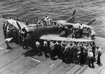SBD Dauntless dive-bomber being spotted on the flight deck of the Enterprise, Jan-May 1942. Note the groove in the outrigged sponson for the tail-wheel, thus spotting the plane while only using deck space for the front portion.