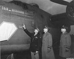 "Col Leon W Johnson points to scoreboard of B-24 Liberator ""Victory Ship"" as LGen Jacob L Devers and LGen Ira C Eaker look on, RAF Shipdham, Norfolk, England, UK, Nov 22 1943. The horizontal bomb represents the low level attack on Ploesti, Aug 1 1943"