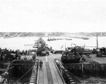 Military vehicles move ashore from Mulberry Artificial Harbor A, across a pontoon bridge, to Omaha Beach, Normandy, France, June 16 1944 (D+10). Visible are M3 Halftracks, an M8 Greyhound, and AFKWX 2�-ton Trucks.