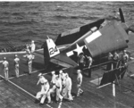 F6F-5 Hellcat rests on the flight deck of USS Bataan as Marine and Navy Honor Guards prepare for a burial at sea off Okinawa, April 18 1945