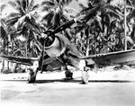 A crewman finds the only shade there is on the airstrip on Green Island (now Nissan Island), Northern Solomons, beneath an F4U-1D Corsair fighter of Marine Squadron 222, 1943-44.