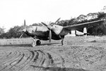 "A P-38 Lightning with the 80th Fighter Squadron, the ""Headhunters,"" at rest at Dobodura, New Guinea, Dec 1943 – Feb 1944. Note the improvised wheel chocks."