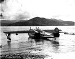 "A PBY-5 Catalina of Patrol Squadron 34, one of the ""Black Cats"" night patrol squadrons, at rest at Samarai Island, New Guinea, Jan-Feb 1944. Note the absence of any markings beyond the squadron patch on the bow and the side number on the tail."