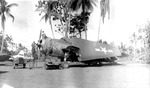 A Marine Corps TBM-1C Avenger of the 7th Fleet Command undergoing some maintenance at the Cyclops aerodrome, Hollandia, New Guinea, Jul-Aug 1943. Note the Jeep and the tail of an Army A-24 Banshee painted as a target tug.