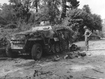 A soldier of the US Army looks at a German half-track camouflaged with branches near Le Neufbourg, France, Aug 12 1944. The half-track SdKfz 251 Ausf D, SS 926256 is from the 1.SS-Panzer-Division Leibstandarte Adolf Hitler. Note the soldiers M3 Grease Gun