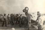 Fire control crews responded to an FM-2 Wildcat that had nosed all the way over on landing aboard training aircraft carrier USS Sable on Lake Michigan, United States, 1944.