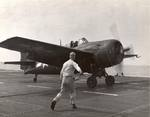 Deck crew signals the pilot of an FM-2 Wildcat aboard the training aircraft carrier USS Sable on Lake Michigan, United States, 1945.