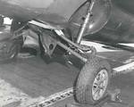 The damaged landing gear of an FM-2 Wildcat after a hard landing aboard the training aircraft carrier USS Sable on Lake Michigan, United States, 1943-45.