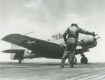 The Deck Officer gives an SNJ-3C Texan the go-ahead to launch from the training aircraft carrier USS Wolverine on Lake Michigan, United States, 26 Apr 1943.