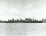 Training aircraft carrier USS Wolverine underway on Lake Michigan with the Chicago skyline behind, 22 Mar 1943.
