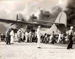Air Station personnel move a damaged PBY Catalina away from burning hangars at Kaneohe Naval Air Station, Oahu, Hawaii, Dec 7, 1941.