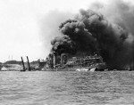 USS Shaw burning in partially sunk Floating Drydock YFD-2, Pearl Harbor, Oahu, Hawaii, Dec 7, 1941. Note men at left playing fire hoses in the direction of the drydock.