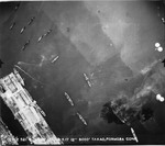Overhead strike photo of bomb splashes and burning ships in Takao harbor (Kaohsiung) on Formosa (Taiwan), Jan 9, 1945