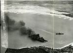 Japanese freighters Shoei Maru beached and burning and Takebe Maru damaged and trailing oil on the coast of French Indochina (Vietnam) north of Qui Nhon after being attacked by 175 USN carrier planes, 12 Jan 1945.