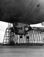 View of the control car of US Navy blimp K-11, Airship Patrol Squadron ZP-11, attempting to land during a storm at NAS South Weymouth, Massachusetts, United States, Sep 27, 1942. Note Hangar One under construction.