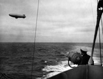 US Coast Guard Cutter Duane exchanging blinker signals with a US Navy K-class airship, 1943.  Both crafts were serving as convoy escorts in the North Atlantic.