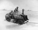 A Jeep being towed ashore at Normandy, France, Jun 12, 1944. Note that censors have deleted markings on the Jeep