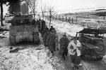 German prisoners of war marching between a disabled M4 Sherman tank and a litter-Jeep, Jan 1945. This is possibly during the Battle of the Bulge but more likely is the Battle of Hürtgen Forest.