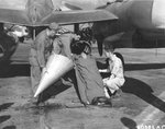 "A ""patient"" being prepared for transport during a drill, 1944. The aircraft is an F-5B Lightning ""Lucky!"" likely with the 28th Photo Recon Sq fitted with two drop tanks modified for use in high speed medevac operations"