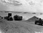 Columns of vehicles transferring supplies up from the beach on Iwo Jima, Mar 10, 1945.
