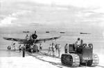 An OS2U Kingfisher float plane being towed ashore at Funafuti, Ellice Islands, mid to late 1942. Note the extremely oversized insignia on the wings.