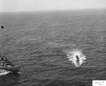 Abandoned by her crew but with engines still running, German U-505 circles at 7 knots as US boarding parties complete the capture and escort USS Chatelain stands by off the West African coast, 4 Jun 1944.