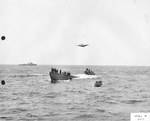 TBF Avenger from Escort Carrier USS Guadalcanal overflying the captured German Type IXC submarine U-505 as a salvage crew assembles on the U-Boat's bow. A US whale boat and an escort stand by, 7 Jun 1944.