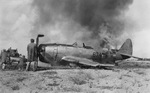 Damage crews dousing the flames after a P-47N Thunderbolt of the 413th Fighter Squadron belly-landed at Central Field, Iwo Jima, Japan, 7 Sep 1945.
