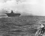 USS Yorktown (Essex-class) steaming in reverse and landing an F6F-3 over the bow during trials, probably in the Gulf of Paria, Jul 1943