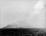 Badly damaged carrier USS Princeton burns as cruiser Reno and destroyer Morrison close in to offer assistance, 24 Oct 1944 as seen from USS Essex off Luzon in the Philippines.