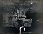 Damage to USS Intrepid's starboard rudder being examined in Pearl Harbor Drydock #1, 26 Feb 1944. The damage was done by an aerial torpedo on 17 Feb 1944 off Truk.