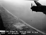 Strike photo taken by aircraft from USS Bunker Hill showing an SB2C Helldiver from Bombing Squadron VB-84 over Miyazaki Airfield on southern Kyushu, Japan, 17 Mar 1945