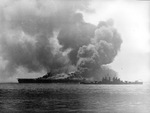 The USS Bunker Hill, burning from two special attack aircraft crashing through the flight deck off Okinawa, is assisted by cruiser Pasadena, 11 May 1945.