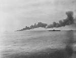 The USS Bunker Hill, burning from two special attack aircraft crashing through the flight deck off Okinawa, 11 May 1945. Note cruiser Wilkes-Barre at extreme left and carrier Randolph at right.