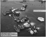 Overhead view of the progress of the salvage work on the sunken battleship USS Arizona in Pearl Harbor, Hawaii, 21 Mar 1943, a year and a half after the attack. Note flag flying from staff amidships.