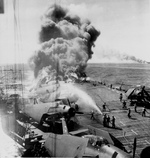 Firefighters of Belleau Wood fighting flames caused by a special attack aircraft, in the Philippine Islands, 30 Oct 1944; note TBM Avenger aircraft on flight deck and Franklin burning in distance. Photo 2 of 2