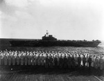 Officers and sailors of USS Saratoga man the rails for HMS Illustrious passing close aboard as the British Eastern Fleet bids farewell to the American carrier, Indian Ocean northwest of Australia, 18 May 1944.