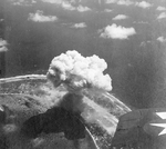 Strike photo of Kwajalein, Marshall Islands taken by aircraft from USS Enterprise, 30 Jan 1944. Note the rising mushroom cloud from the exploding Japanese ammunition dump.