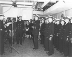 Captain Warren K Berner, left, reading his orders to take command of the training carrier USS Sable at her commissioning ceremony at the American Shipbuilding Company in Buffalo, New York, 8 May 1943.