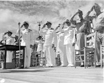 Admiral Chester Nimitz, Rear Admiral Marc Mitscher, and others salute the National Anthem during Sunday morning colors at Kaneohe Naval Air Station, Hawaii, 8 Nov 1942