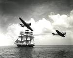 US Navy SNJ Texan training aircraft making a low level pass near a three-masted sailing ship, probably along the east coast of the United States, 1942