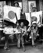 US soldier, Chinese soldier, and Chinese guerrilla fighters displaying captured Japanese flags, Browning machine guns, and MP 34 submachine gun, China, 1940s