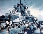 A Roman Catholic chaplain performing mass on the deck of USS Iowa as they closed on the Mariana Islands, Jun 1944. Note the colors of the ship's paint and the 40mm and 20mm anti-aircraft mounts.