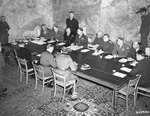 Officers gather around a table at Eisenhower's headquarters to sign the instruments of the German surrender, Reims, France, 7 May 1945. Photo 2 of 2