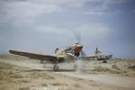 Kittyhawk Mark III fighter with the RAF 112 Squadron taxiing at Medenine, Tunisia, May 1943. The crewman on the wing is helping guide the pilot whose view is obscured by the aircraft's raised nose.