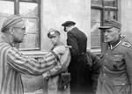 After being liberated by the US 1st Army, a Russian prisoner points out one of the particularly brutal guards at Buchenwald, Germany, 14 Apr 1945. Note guard's black wound badge indicating he is combat wounded.