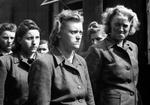 Female SS guards at Bergen-Belsen are detained by the liberating force, 21 Apr 1945.
