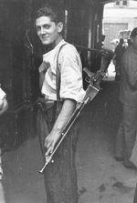 Polish resistance fighter, Warsaw, Aug 1944; note ZB vz. 26 light machine gun at shoulder and unidentified pistol in holster